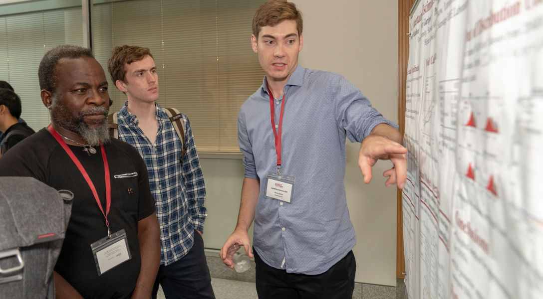 A student explains his research during a poster session held in conjunction with the 2018 Cornell Day of Statistics.