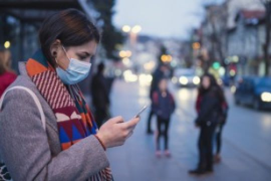A woman, wearing a medical mask, looks at her smartphone.